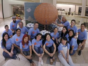 Architects Orange members pose in front of their sculpture Rising Above Hunger built for the Canstruction charity fundraiser.